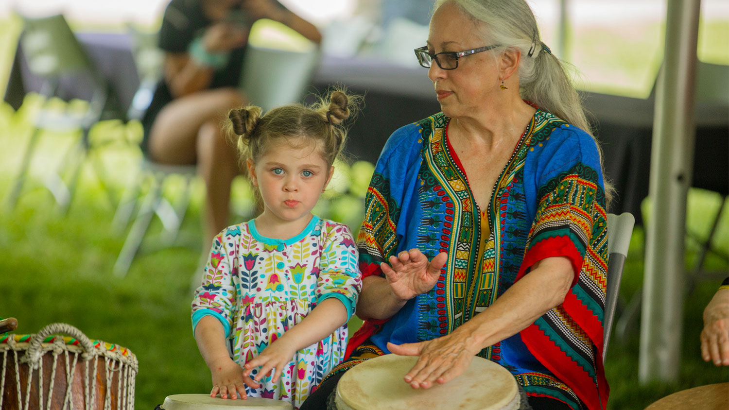 Adult and child playing conga drums