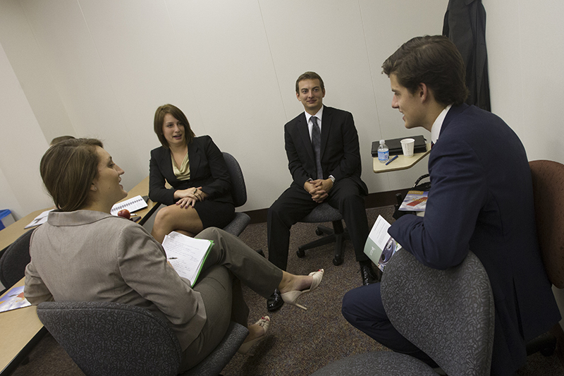 Four students, seated, in business attire