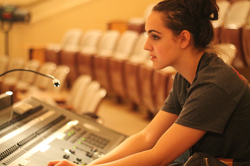 student works the sounds board at a production