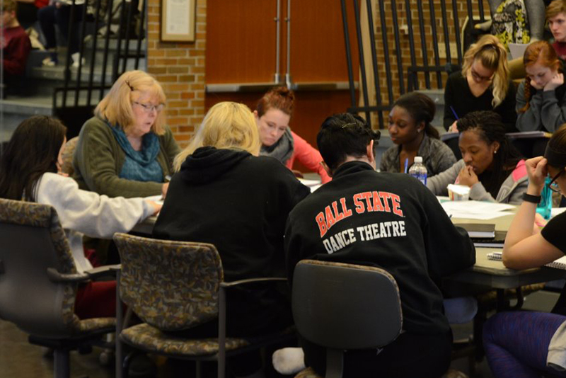 dance faculty works with students around table