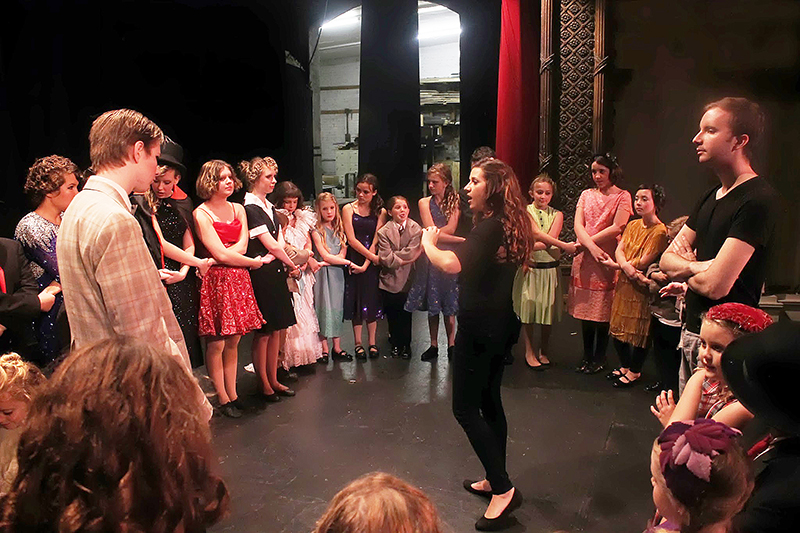 theatre education students in a circle backstage