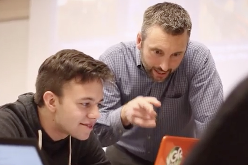 tyler smith instructs student at a computer