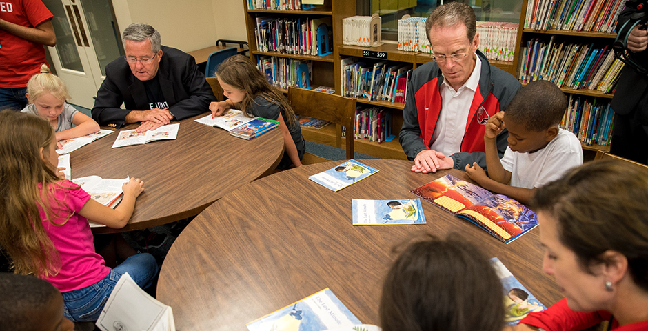President Geoffrey S. Mearns, his wife, Jennifer, and Ball State Trustee Brian Gallagher reading to students during Better Together