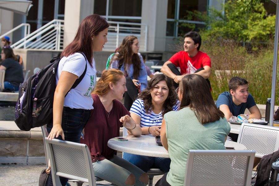 students gathered around a table outside the Atrium