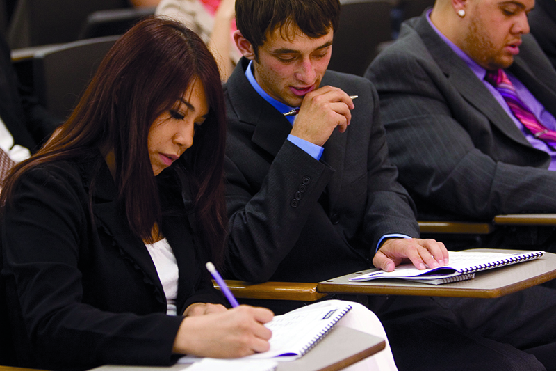 Busines students taking notes during class
