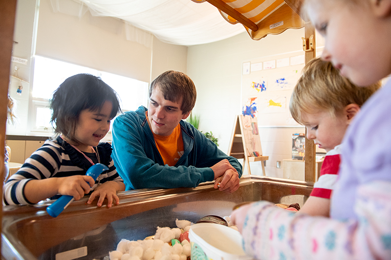 Students work with young children at the Mitchell Center