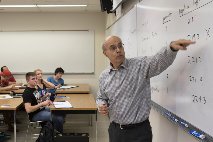 Professor lecturing at a whiteboard