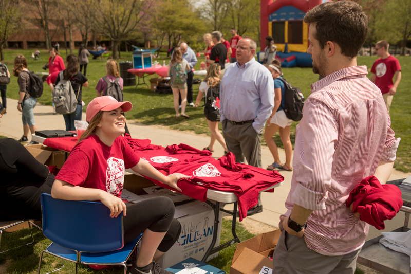 Students hand out T-shirts at Miller Day on campus