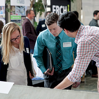Student talking to firm representatives at the Job and Internship Fair