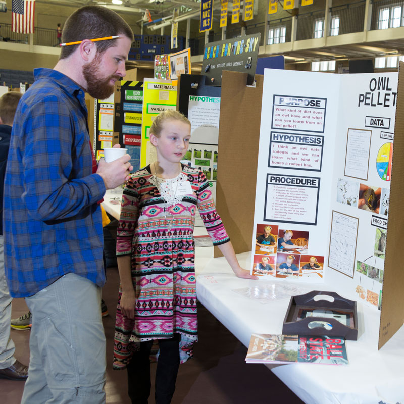 man and girl looking at a poster at a science fair
