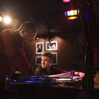 Mark Buselli and Brent Wallarab standing and sitting at a piano working on music