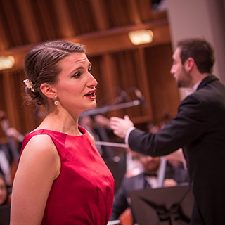 a vocal soloist with conductor in background
