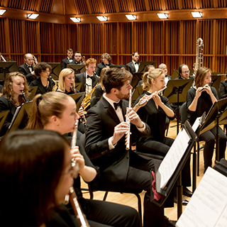 Members of a concert band performing on stage