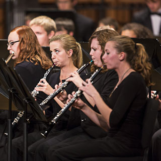 Three female oboist performing with other band members in the background