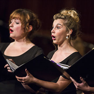 Two female vocalists, one blond and one redhead, singing during a choir concert