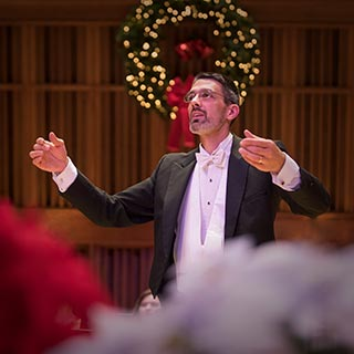 Conductor Andrew Crow leading the choral ensembles on the Holiday Choral Concert