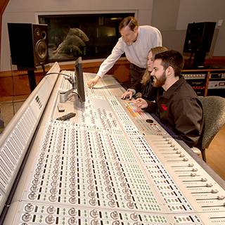 Recording engineers at a mixing board