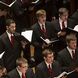 A group of men in black suits, white shirts, and red and black striped ties performing in the Statesmen choral ensemble
