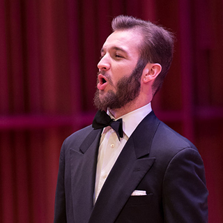 A male vocal soloist singing on stage
