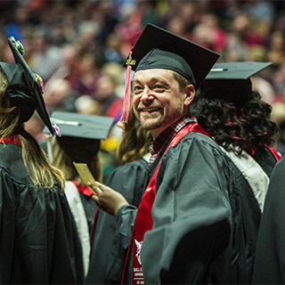 A graduate smiles at Winter commencement