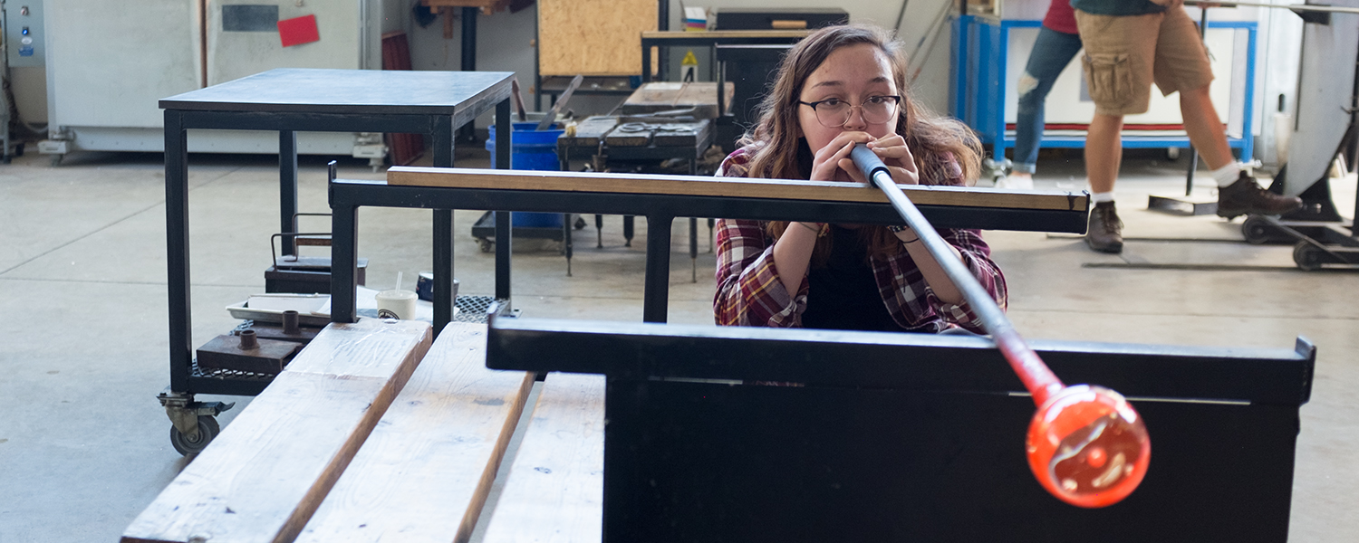 female student blowing glass in the Marilyn K. Glick Center for Glass
