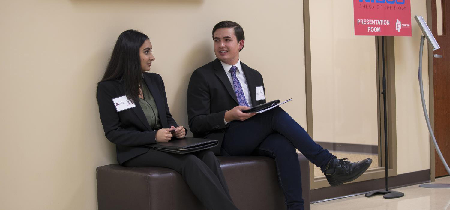 Two students speaking, in business attire