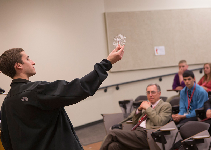 A student lifts up an object he created during the Congressional Leadership Academy