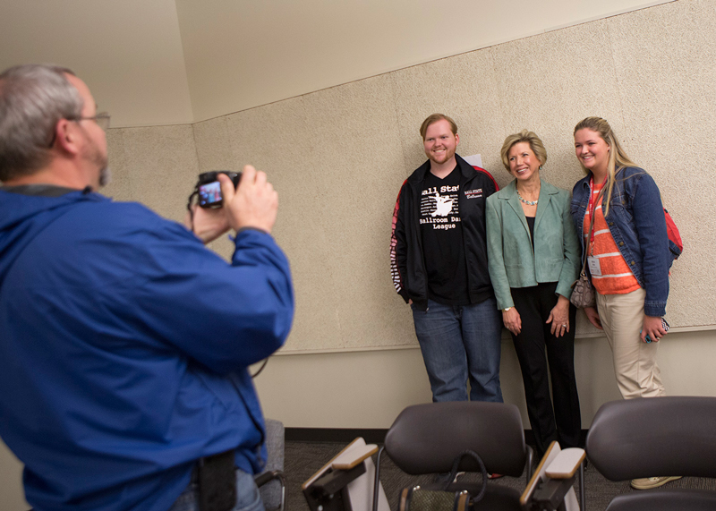 A photographer takes a picture of two students with President Jo Ann Gora