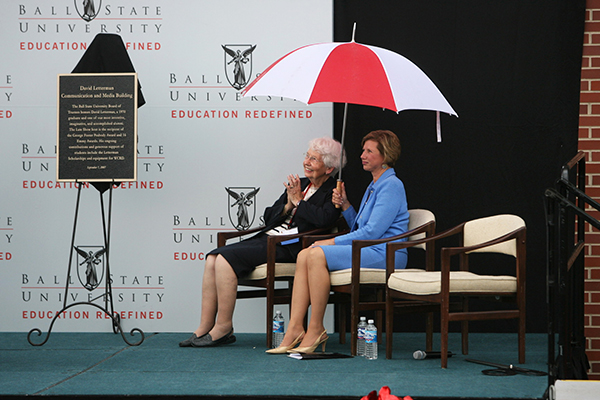 President Gora seated next to Dave Letterman's mom with umbrella