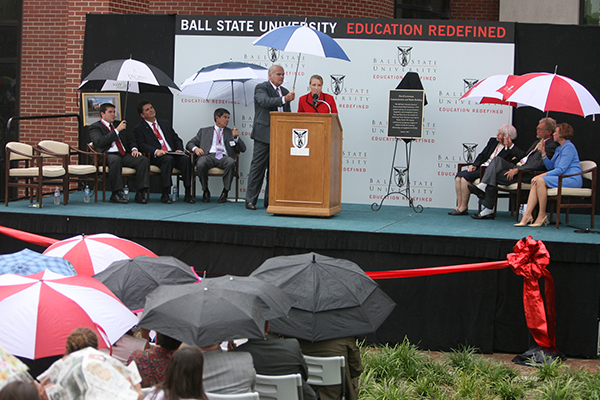 University officials on stage holding umbrellas during rainfall