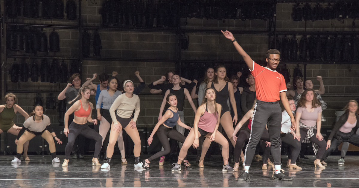 A Chorus Line cast members dancing on stage