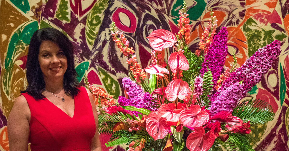 First Lady Janet Holcomb with one of last year's floral designs from the David Owsley Museum of Art's Art in Bloom event.