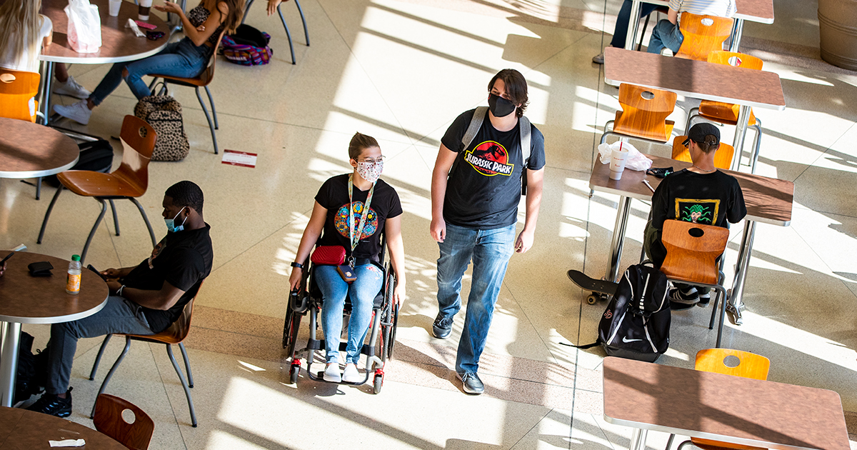 A student in a wheelchair with a friend