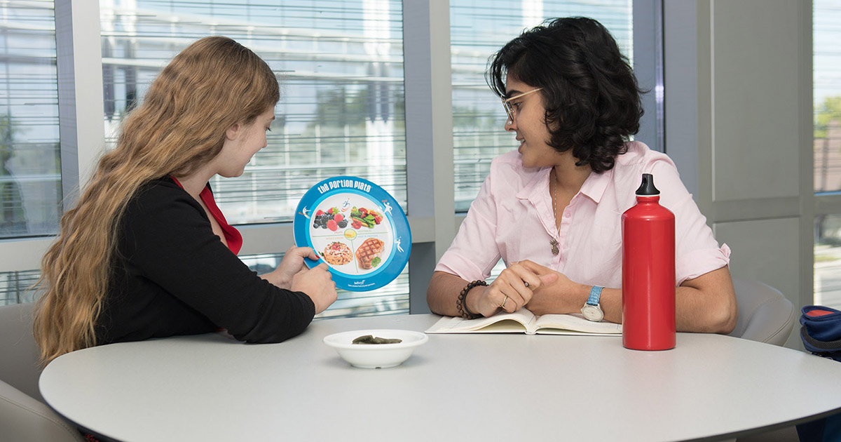 A dietetic intern works with another student